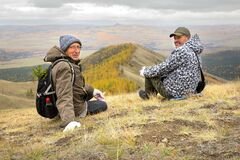 two mature tourists at the top of the ridge admire the Ural mountains and taiga
