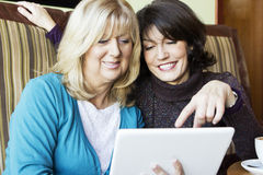 Two mature woman digital tablet Stock Images