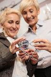 Two mature women choosing prescription lenses to match with new reading glasses. Selective focus on foreground, blurred faces in the background royalty free stock photo