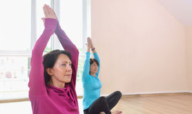 Two mature women doing yoga exercise in fitness studio Royalty Free Stock Image