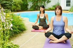 Two mature women keeping fit by doing yoga in the summer Stock Photo