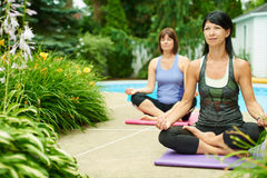 Two mature women keeping fit by doing yoga in the summer Stock Photos