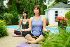 Two mature women keeping fit by doing yoga in the summer Royalty Free Stock Images