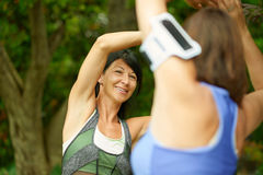 Two mature women keeping fit and streching before jogging Stock Photography