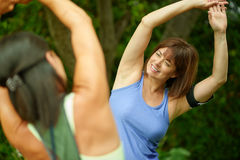 Two mature women keeping fit and streching before jogging Royalty Free Stock Images