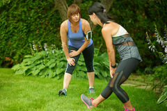 Two mature women keeping fit and streching before jogging Royalty Free Stock Image