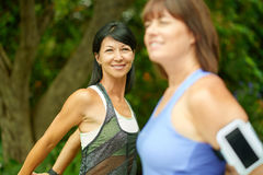 Two mature women keeping fit and streching before jogging stock photo