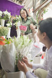 Two Mature women Looking At Flowers In Flower Shop Stock Image