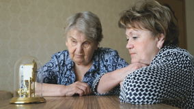 Two mature women looking at the table clock. Portrait shot of two women looking at a table clock wondering about the time passed and time left stock video