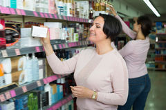 Two mature women picking cream from shelf Royalty Free Stock Images