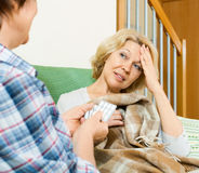 Two mature women with pill on couch Royalty Free Stock Photography