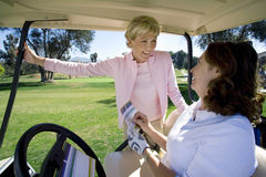 Two mature women playing golf, brunette sitting in golf buggy, filling out scorecard, blonde standing beside buggy, smiling Royalty Free Stock Photography
