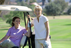 Two mature women posing on golf course, brunette sitting in golf buggy, blonde standing beside her, smiling, portrait Stock Image
