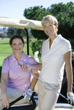 Two mature women posing on golf course, brunette sitting in golf buggy, blonde standing beside her, smiling, portrait Royalty Free Stock Photos