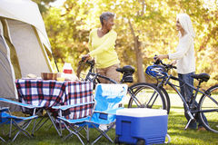 Two Mature Women Riding Bikes On Camping Holiday Stock Image