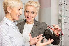 Two mature women shopping and choosing prescription eyeglasses. Two mature women shopping for prescription eyeglasses, choosing between different models on a royalty free stock image
