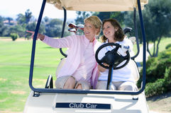 Two mature women sitting in golf buggy on golf course, brunette driving, blonde pointing, smiling, front view Stock Photos