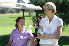Two mature women talking on golf course, brunette sitting in golf buggy, blonde standing beside her, smiling Royalty Free Stock Photography