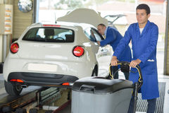 Two mechanic repair and cheking climate on car Stock Photos