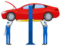 Two mechanic standing under underbody and repairing a car lifted on auto hoist Stock Images