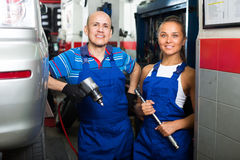 Two mechanics in car fixing workshop Stock Photos