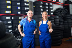 Two mechanics in car fixing workshop Stock Images