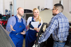 Two mechanics and car owner. Two mechanics a men and a beautiful women dressed in a workwear at a car service center are explaining their client maintenance plan Royalty Free Stock Photos