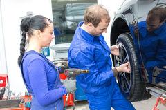 Two mechanics changing a wheel on a car Royalty Free Stock Photography