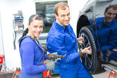 Two mechanics changing a wheel on a car Royalty Free Stock Photos