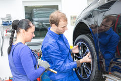 Two mechanics changing a wheel on a car Royalty Free Stock Images