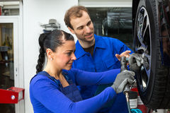 Car mechanics changing wheel working on hydraulic lift Stock Photography