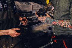 Two mechanics fixing car`s engine parts. Close up image of two mechanics with tattoos on arms, fixing car`s engine parts in a workshop Royalty Free Stock Image