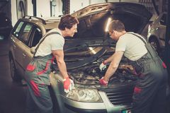 Two mechanics fixing car Royalty Free Stock Photos