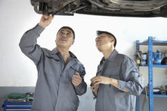 Two Mechanics Looking at Underside of a Car, Discussing Royalty Free Stock Photos