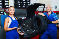 Two mechanics operating wheel equilibrium control machinery at auto workshop. Two positive smiling mechanics operating wheel equilibrium control machinery at Stock Image
