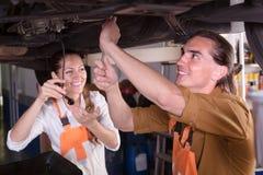 Two mechanics repairing car Royalty Free Stock Images