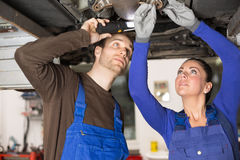 Two mechanics repairing a car in hydraulic lift Royalty Free Stock Photography