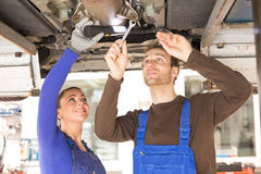 Two mechanics repairing a car in hydraulic lift Stock Photos