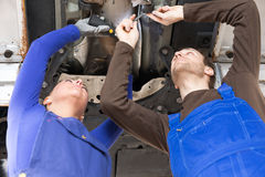 Two mechanics repairing a car in hydraulic lift Stock Images