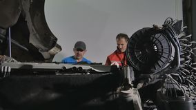 Two mechanics searches the breaking in motor of truck. Two auto mechanics repairs motor of truck at car service station. The man holds a lamp and lights it stock footage