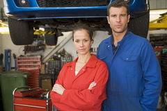 Two mechanics standing in garage Stock Photos