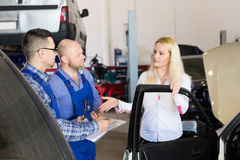 Two mechanics trying to cheat client at workshop Royalty Free Stock Image