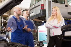 Two mechanics trying to cheat client at workshop Stock Image
