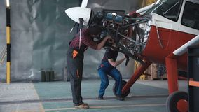 Two mechanics working on a small aircraft stock footage
