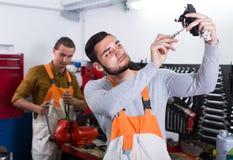 Two mechanics in workshop. Two professional mechanics working in locksmiths workshop Royalty Free Stock Photo
