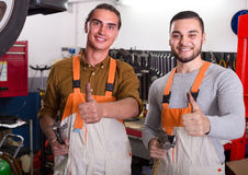 Two mechanics in workshop. Two mechanics toiling in locksmiths workshop and smiling Stock Images