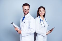Two medic colleagues in white coats on pure background, holding. Clipboard and tablet. They are so successful, smile and work in team together royalty free stock image