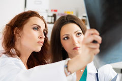 Two medical doctors looking at x-ray image Stock Photo