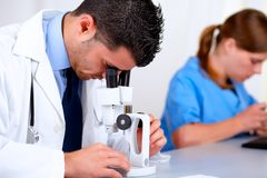 Two medical doctors working at laboratory. Portrait of two medical doctors working at laboratory at hospital using a microscope Stock Image