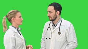 Two medical professionals discuss with a patient on a Green Screen, Chroma Key. Two medical professionals discuss with a patient. Close up on a Green Screen stock video footage